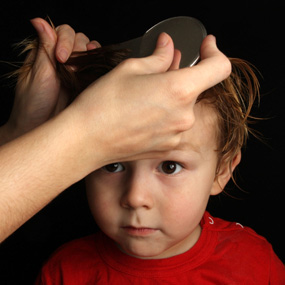 treating headlice start with the hair - picture of a little boy having his hair nit combed